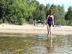 Redhead milf Mina Gorey, wearing a swimsuit, is having fun outdoors in reality video. She swims in a lake and gives an interview.