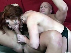 A vivacious cougar with long red hair, big fake tits and a fabulous body enjoys sucking a stranger's huge cock on her couch.