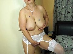 This dirty mature is looking sexy with her stockings and garters. She has a floppy pair of natural boobs and very bumpy, puffy nipples. She sticks her fingers in her old cunt, and she makes herself cum.