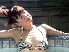Mature slut Cindy gets into piscine after a long day so that she can relax in the water. the bubbles feel good on her skin. She takes off her bikini top and reveals her supple breasts. She plays with her boobs.