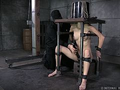 This master loves to torture and humiliate her slave. She is locked in a chair which restrains her and she has a bucket put on her head. The bucket has a face drawn on it. She uses a vibrator on her cunt, which makes the slaves toes curl up.