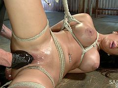 Dirty slut Alexa is tied up in rope and controlled by her cruel master. At first she is hanging from the ceiling, but the master lowers her so he can finger blast her. The rope is so tight that the slaves's tits are bulging. Master sticks his whole hand in her pussy and uses a vibrator on her cunt, too.