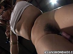 Tied Asian tortured and toyed wildly. Outstanding Japanese babe has her delicate body bound with a coarse rope. She moans while her kinky lover is banging her with a fat dildo.