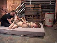 Patrick is an unlucky slave that is tied up in the doorway of the dungeon so that the master can squeeze his cock firmly and whack him off. The master drags the rope bound slave to a dingy mattress in the basement and tugs him off some more.
