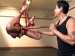 Watch as this gay slave is tied up in red rope and hanged from the ceiling. He's dangling there and his cock is flopping around so the master grabs it firmly and sucks him off. Now the slave is going to get violated with a pole.