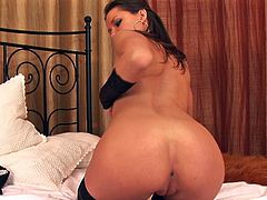 Stacked brunette bitch in stockings performs hard solo in bed