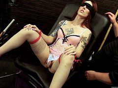 This redhead shemale slut is in the dungeon and her master is going to have his way with her. She gets her cock and asshole played with, while she is tied to the chair by her ankles. She is blindfolded, so she can't see how she is being toyed with. The master rubs sex toys all over her body.