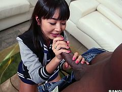 This Asian cutie is on the couch, masturbating herself with a flesh colored dildo. She shoves it deep in her cunt, but when it is compared to her friend's big black cock, the didlo is miniscule. Will she be able to handle choking on and sucking on this massive black penis? She sucks the tip and stokes the shaft.