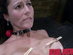 This nasty slave is fucked hard in her wet cunt and the mix of pleasure, and pain is amazing to her. Her nipples are pinched with wooden clamps and she bends over, to be fucked even more. Her mouth is covered in spit and she has a dick, thrusted down her throat.