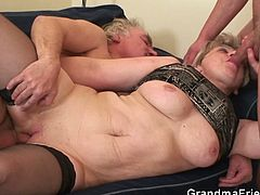 This granny started to rub her cunt when a young man entered the room and saw her. She gave him a blowjob and meanwhile her husband showed up. They fucked her from both ends.