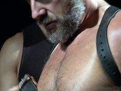 It is BDSM time featuring this bearded stud as he is only wearing his briefs and his master preparing him up by tying him up with his hands and feet are locked before touching his cock.