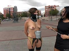 Sandra is a a mistress, who loves to humiliate her subject publicly. That's why she tied up her bitch Camil and walks her around naked. She tied her hands and mouth with latex collar and chains, and walks her around, to find a good place to get her fucked the way she deserve.
