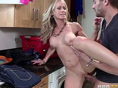 Xander is fucking his neighbor's wife in the kitchen, but little do they know that the cute, young blonde stepdaughter is around the corner, watching the dirty action. The milf gets on her knees to suck on his big cock and then, she lifts her leg up on the kitchen countertop, so he has easy access to her pussy.