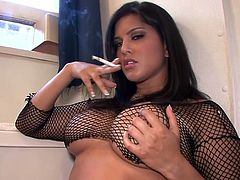 Sassy chick in fishnets Sunny Leone smoking and masturbating at the same time