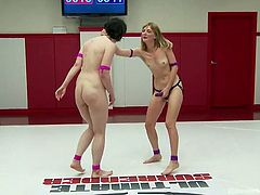Brunette contestant Pink, gets multiple fingering and groping from her blonde opponent Mona, and apparently loses the naked lesbian wrestling match. Winning the match, turns the beautiful blonde into a dominating Mistress and, wearing the trophy strap-on, she starts fucking Pink's mouth and pussy hard.