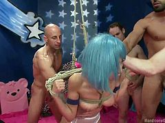 A horny lady wearing a blue wig and sexy white stockings, gets tied up strongly in a creative rope bondage. Watch the slim bitch with small tits sucking cocks and getting pounded hard by a gang of five angry guys, that use her shamelessly. She seems to enjoy. Dare to click and see all.