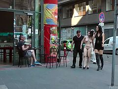 It has been decided, that slutty Chiara deserved to be disgraced in public. There's no better way to humiliate this brunette bitch, than walking her completely naked and mouth gagged through the streets... Once they arrive in a clothes' shop, her angry guardians persuade the naughty babe into sucking cock. See!