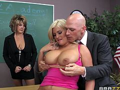 Julie has been a bad girl and her teacher decides it's time to punish the hot blonde slut, using some unorthodox methods. See the bald guy slapping the busty lady's crazy ass, as she bends over the desk, to show her appetizing buttocks. Also, watch her obediently getting on knees, to offer an exciting blowjob.