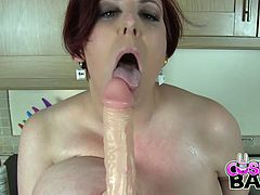 Mature redhead bitch with huge jugs plays with fake cock at kitchen