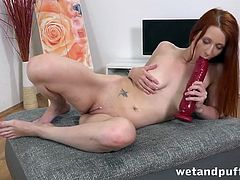 Big toys stretch the holes of a sexy redhead