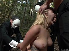 A blonde bitch with fascinating big tits, runs through the woods, to get rid of the masked guys, who follow her. See what happens to her, while she gets caught by the horny men! While her hands are tied with rope, a big dick is stuffed down her throat, making her gag. Enjoy the naughty moments...
