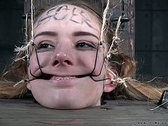 Jessica is in a very unique situation here. The young, beautiful, metal-mouthed slut is in an big oil drum with only her head exposed. Her executors have hooks attached to wires, which they are putting in her mouth, stretching and pulling her lips and nose. They also use a pair of tongs to pull her tongue.