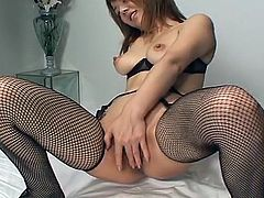 Short haired chick from Japan in fishnet stockings tickles her own cunt