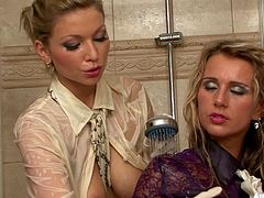 A couple of fully clothed chicks have some lesbian fun in the shower