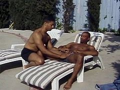 The Dennis twins, called so because both of them are named Dennis, are just sitting out in relaxing chairs, getting some sun on their buff bods. Within seconds it seems, the darker Dennis gets his pants off, inviting the lighter Dennis to blow him. He takes that opportunity, swallowing every inch.