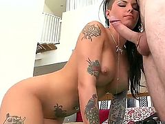 A lovely brunette with large tits, Christy Mack, is on her knees, on the rug. She is giving a blow job and is also spreading her shaved pussy lips.
