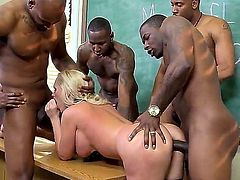 Blonde milf is doing some work as a teacher. She is assigned with some large black students. She calls them to stay after class to have group sex.