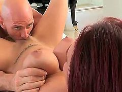 Johnny Sins is with a redhead that has nice natural tits and tattoos on her body. He is feeling her knockers to make sure that they are real while he licks her pussy.