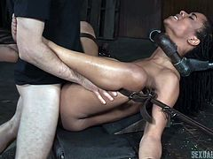 Kira's beautiful milk chocolate body is tightly attached to Jack and Maestro's homemade device, which chokes her, while she's on her back with her legs spread. The two executors take turns pounding her snatch, until she's broken.