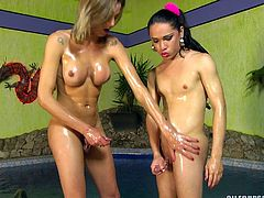 Watch as these sexy trannies rub each other sensually and pile loads of oil all over their bodies. The sensuality makes their dicks stand straight up. They chill by the water and masturbate together sexily.