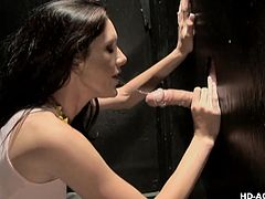 brunette milf sucks big cock sticking out of the wall