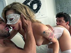 Waiting for sexy Dahlia to show up is really worth! The tattooed blonde wears a carnival mask and kinky white lingerie. Her provocative attitude is enough to make these two guys hard. While one of them stuffs his dick down her throat, the other one bangs her wildly, from behind. See the exciting details.