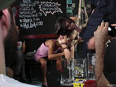 Nikki Litte, brunette tiny teen, is hanging like a piece of sausage, in the middle of the beerhouse. Suspended from the ceiling, bonded with ropes, she is available for every angry dick. Watch Nikki sucking dicks, while being watched by the loud crowd. Have fun and enjoy the inciting details!