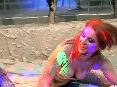 Raging girls get to a muddy arena for a fierce wrestling in a close up shoot