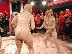 Nude ladies wrestle fairly in a muddy arena with a big crowd cheering