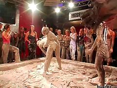 Slutty dames fight unceremoniously in a muddy arena with a huge crowd