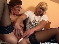 A redhead grandma in glasses and sexy stockings sucks and fucks a young man in his bedroom.