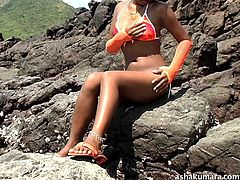 Asha Kumara is desired by millions, and that's just in her home country! The dark-skinned beauty is sitting on the rocks in her bikini, skin drinking in the hot sun. She rubs herself through her bikini bottom, to get the juices flowing.