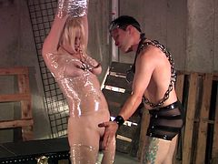 This lady here is the subject of this guy's fantasy for domination. He's a little weird about it, considering his garb and how he decides to punish and tease her, but to each his own. Enjoy this shrink-wrapped, nipple clamped beauty.