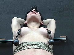 Weighted nipple clamps give her pain, this bondaged brunette cannot stop feeling uncomfortable and yet so incredibly horny. After her big tits get tortured, her master decides it's time to make her know what happens, when a candle is lit in his dungeon. She looks lost and shocked, but also so horny