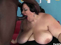 Sucking the black cock with delight. It is large enought to par with her gigantic boobs and plump pussy.