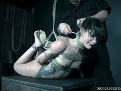 Eden is hogtied and would be suspended in midair if not for the table just underneath her. The sexy inked beauty gets zapped by her executor, making her smile rather than cry out in pain. The more it hurts, the more she smiles!