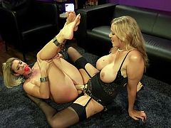 The busty blonde milf, Julia Ann, fingers her lover's wet pussy and sticks a huge plastic cock deep in her cunt. India Summer's legs and arms are bound by metal handcuffs, so she can't even move and she has to take this punishment with loud moans...