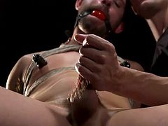 Today, Casey Jacks gets some special pleasures from his dominating gay lover, Alex Mecum. He is tightly bound with ropes and tied to a special wooden device, naked, with metal clamps on his nipples and with a ball gag in his mouth. Now it's time for this electric cock torture...