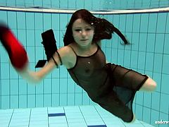 Hot Kristy Russian teen swimming in the pool in the see through fishnet dress